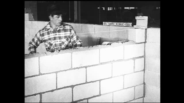 two workers, one young and one old, measuring something with a pendulum; man laying cement for a brick wall - 1940 1949 stock-videos und b-roll-filmmaterial