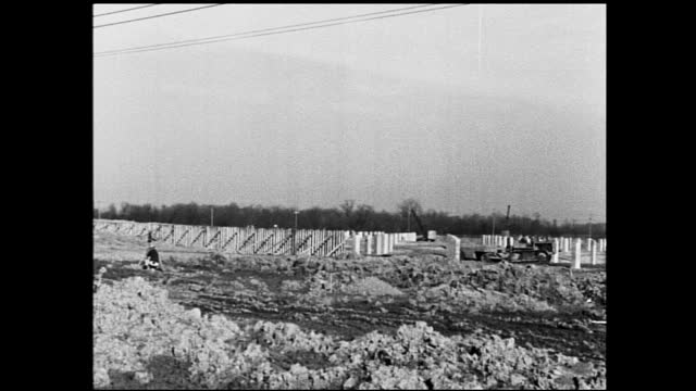 vidéos et rushes de two workers overseeing drill mounted on the back of jeep and drilling in the ground at construction site; tractor driving away in the distance of a... - 1940 1949