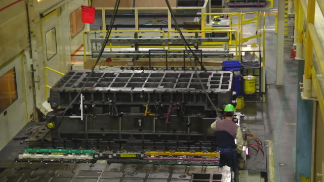 MS Two workers preparing to moving dies from stamping presses in an auto assembly plant / Princeton, Indiana, United States