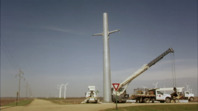 WS Two workers raising a wind turbine at a rural intersection/ Buffalo Ridge, Minnesota