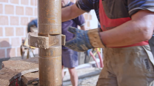 ld two workers screwing an additional drill pipe onto the water well drilling rig - drilling rig stock videos and b-roll footage