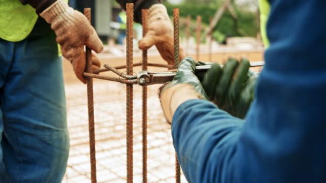 zwei arbeiter binden bewehrungen für die betonpfeiler - architektonische säule stock-videos und b-roll-filmmaterial