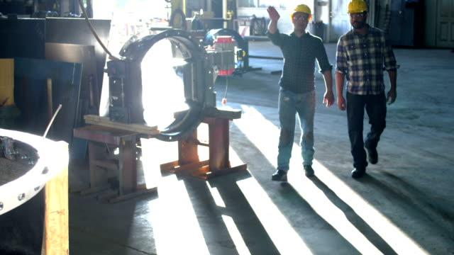 two workers walking through metal fabrication shop - mid adult men stock videos & royalty-free footage