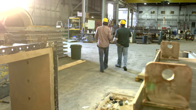 two workers walking through metal fabrication shop - owner stock videos & royalty-free footage