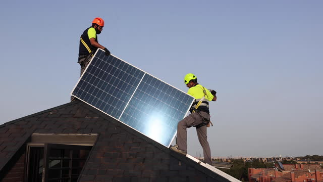 two workers wearing face masks install solar panels on the roof of a residential house on march 31 in majadahonda, madrid, spain. - installing stock videos & royalty-free footage