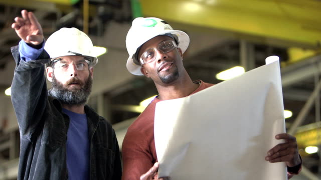 zwei arbeiter tragen schutzhelme, pläne zu betrachten - grundriss stock-videos und b-roll-filmmaterial