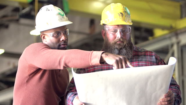two workers wearing hardhats, looking at plans - minority groups stock videos and b-roll footage