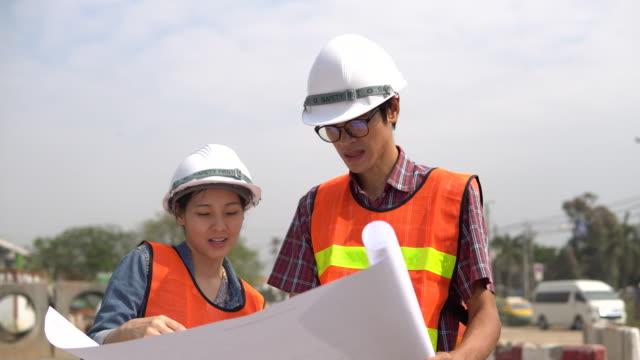Twee werknemers dragen van hardhats, op zoek blauwdruk