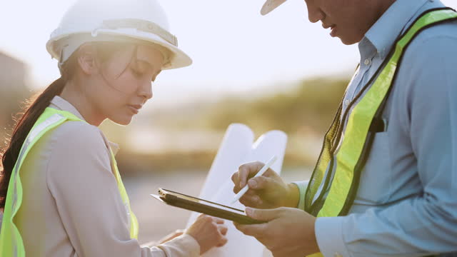 two workers wearing hardhats, looking digital tablet - construction worker stock videos & royalty-free footage