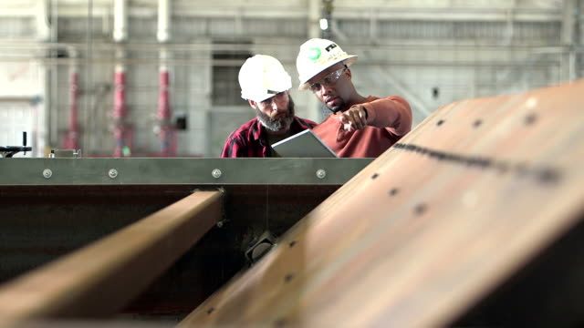 two workers wearing hardhats, looking digital tablet - officina video stock e b–roll