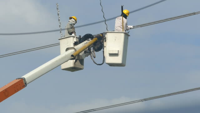 Two workers wearing helmets renovating powerline.