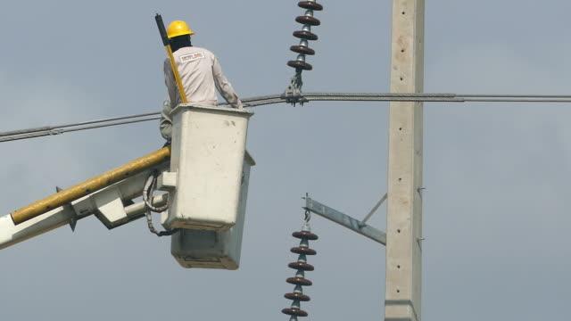 Two workers wearing helmets renovating powerline.