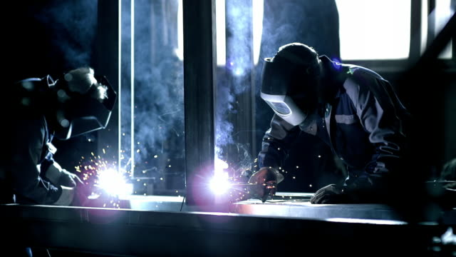 SLO MO Two workers welding a metal frame