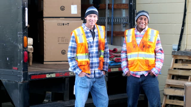 Two workers with a truck delivering boxes
