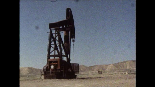 two working pumpjacks in barren landscape - bbc archive stock-videos und b-roll-filmmaterial