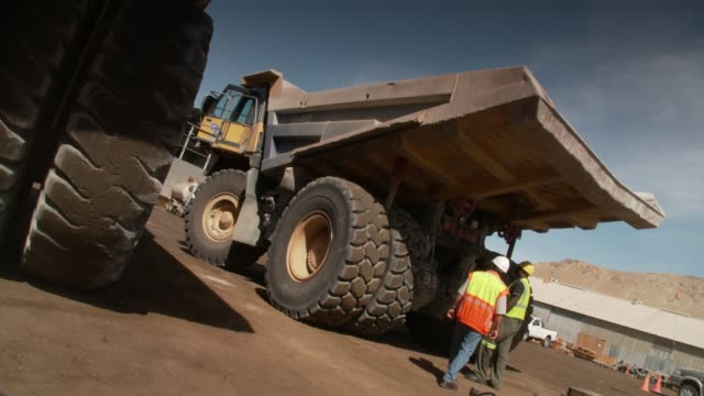 two workmen examine the tires of a large dump truck. available in hd. - 石切場点の映像素材/bロール