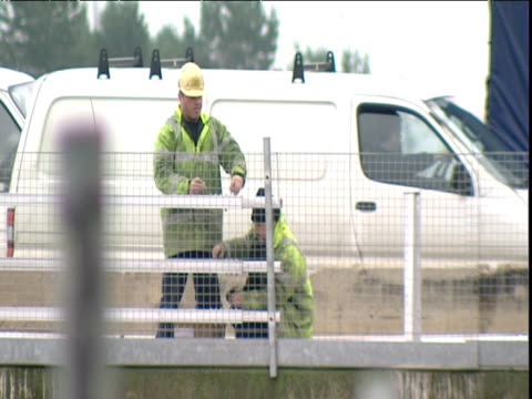 two workmen in fluorescent jackets and hard hats attach wire mesh to roadside safety fence a third man passes behind with a crow bar - wire mesh fence stock videos & royalty-free footage