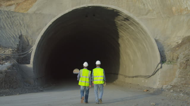 ws two workmen walking into tunnel portal in road construction site, rear view - roadworks stock videos & royalty-free footage