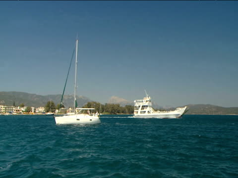 two yachts sail away from each other in blue sea mountains in background - other stock videos & royalty-free footage