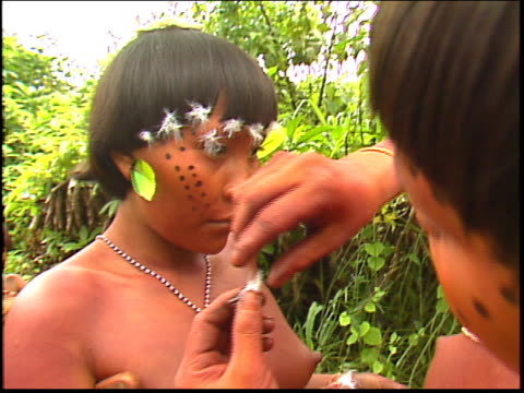two yanomami indian women apply decorations in the amazon - yanomami stock videos and b-roll footage