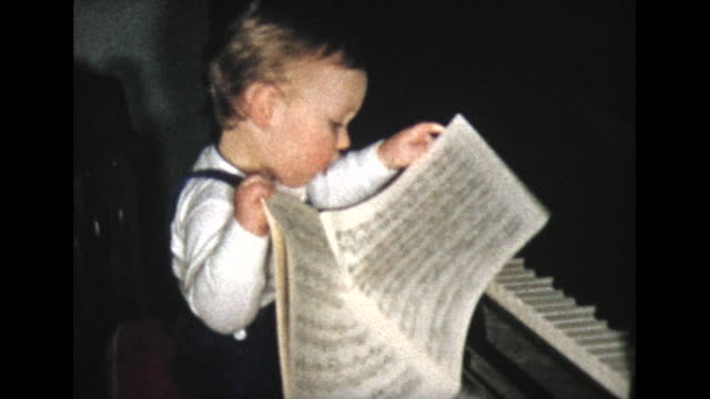 vídeos de stock e filmes b-roll de 1957 two year old boy at piano for first time - pianista