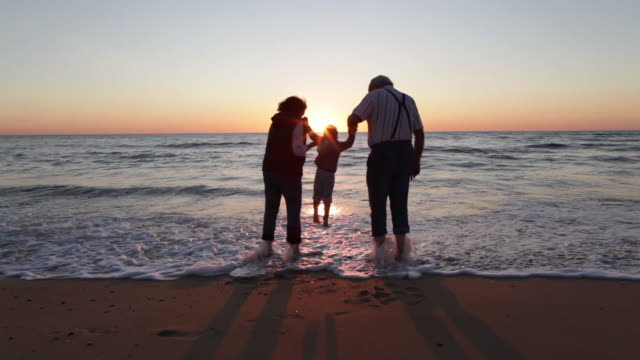 two year old boy walking with his grandparents on the beach in southern france. - lingerie stock videos & royalty-free footage