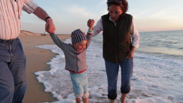 two year old boy walking with his grandparents on the beach in southern france. - familie mit mehreren generationen stock-videos und b-roll-filmmaterial