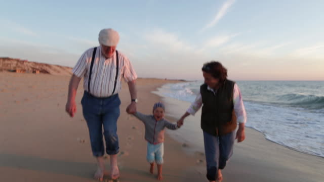vidéos et rushes de two year old boy walking with his grandparents on the beach in southern france. - famille multi générations