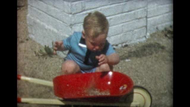 1957 two year old boy with red wheel barrow