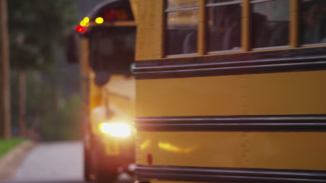 vidéos et rushes de two yellow school buses loaded with school children drive toward camera early in the morning. - bus