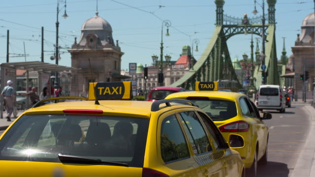 vidéos et rushes de two yellow taxis idle by liberty bridge while traffic and pedestrians go by - yellow taxi