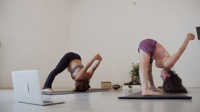 two yogi girls are training together during an online yoga class - home workout stock videos & royalty-free footage