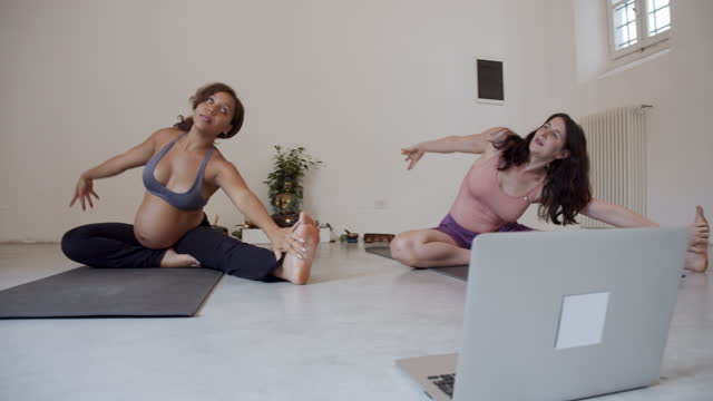 two yogi girls are training together during an online yoga class - pilates stock videos & royalty-free footage