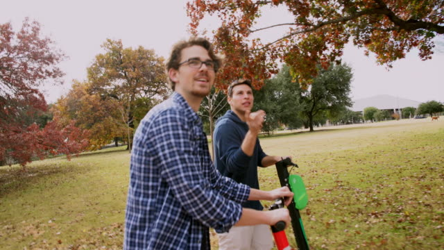 two young, about 30-years-old, male friends, latino, and caucasian white, riding the rental electrical scooter in the colorful autumn park. - austin texas stock videos & royalty-free footage