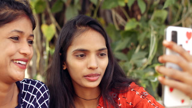 vídeos de stock, filmes e b-roll de two young adult indian female friends using smart mobile phone for a video chat as they gesture with hand signs in conversation using app based browse internet wifi for communication with friends and family during covid-19 - smart