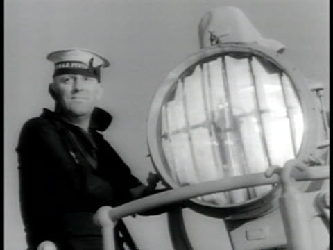 two young adult male sailors standing outside. sailor sending message w/ signal light. sailors turning gun turret. sailor polishing gun barrels of qf... - britisches militär stock-videos und b-roll-filmmaterial