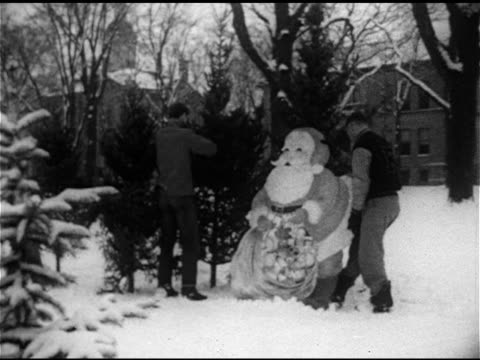 two young adult males w/ evergreen trees outside next to santa claus yard decoration possibly decorating or setting up tree sale area midwestern... - 1952 stock videos & royalty-free footage