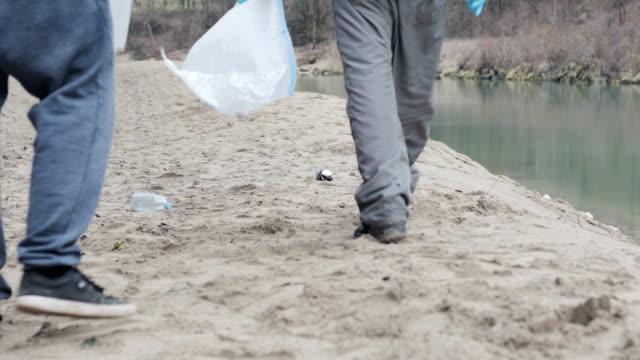 川岸に 2 つの若い成人男性 picknig をゴミ箱 - ゴミ袋点の映像素材/bロール