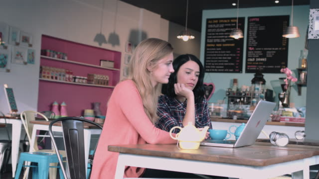 Two young adult women working in cafe on laptop