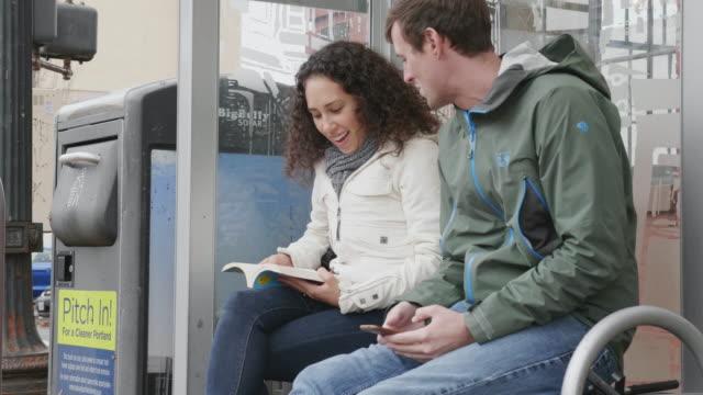 Zwei junge Erwachsene, die im Chat an der Bushaltestelle