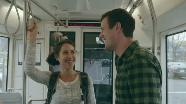 Two Young Adults Chatting While Riding a Streetcar