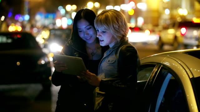 Zwei junge Erwachsene spielen mit tablet in Stadt bei Nacht