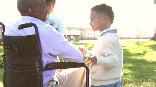 two young african american children run to grandfather - wheelchair stock videos and b-roll footage