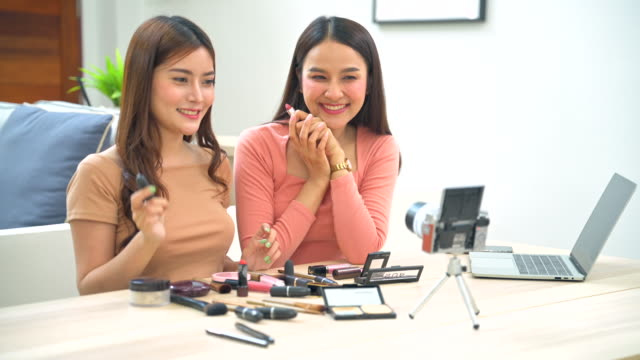 two young asian beauty women blogger present and review beauty cosmetics while sitting in front camera for recording video and broadcast live video to social network by internet. work at home concept - tutorial stock videos & royalty-free footage