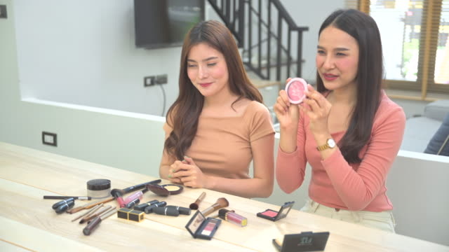 two young asian beauty women blogger present and review beauty cosmetics while sitting in front camera for recording video and broadcast live video to social network by internet. work at home concept - live broadcast stock videos & royalty-free footage
