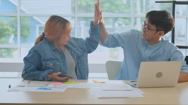 Dos jóvenes asiáticos creativos hombre y mujer mano aplaudiendo después de nuevo, personas en la vida de oficina, emoción de éxito