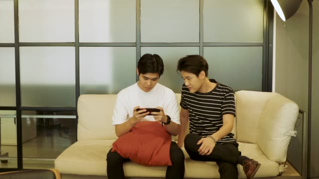 Two young Asian happy friends having fun play games on smartphones at office together after work