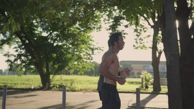 stockvideo's en b-roll-footage met twee jonge aziatische mensen die opleiding in een mooie zonnige dag in ochtend op straat lopen. - sunny