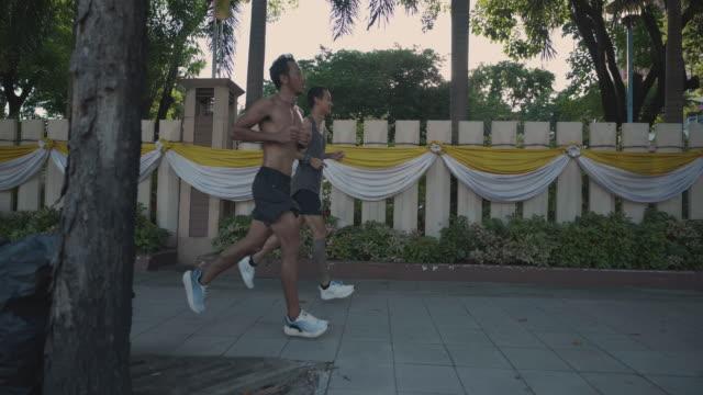 vídeos de stock e filmes b-roll de two young asian men running training in a beautiful sunny day in morning on street. - andar depressa