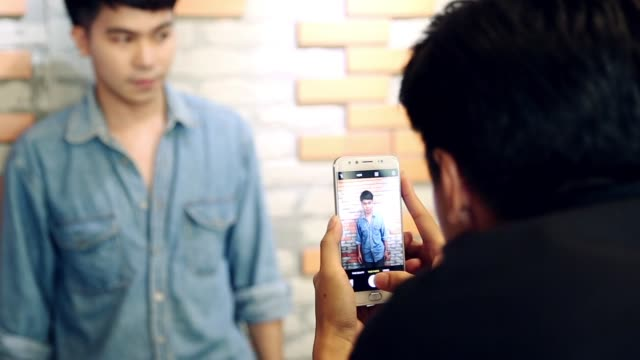 two young asian men with his friends talking photo with smartphone - human face photos stock videos & royalty-free footage